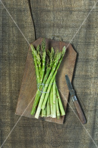 A bunch of green asparagus on a wooden board (seen from above)