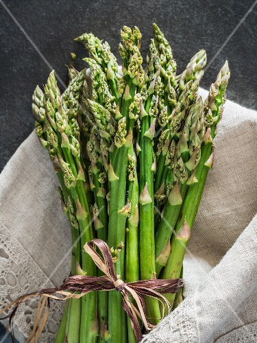 A bundle of green asparagus in a linen cloth