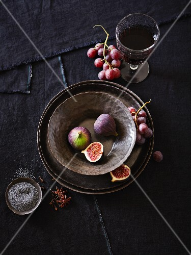An arrangement of crockery with figs, grapes, spices and wine