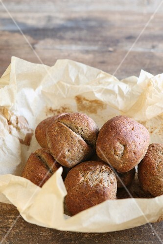 Home-baked, gluten-free buns with flax seed in nest of baking paper