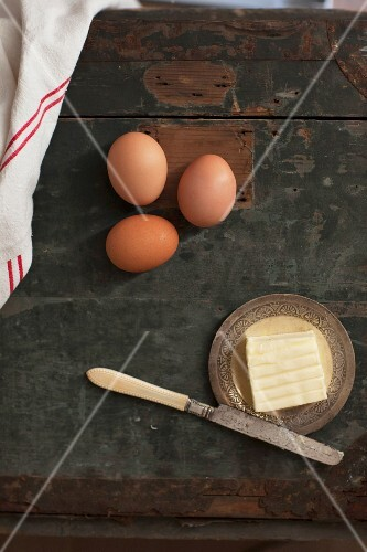 A rustic arrangement of eggs and butter with a knife on a wooden table (seen from above)