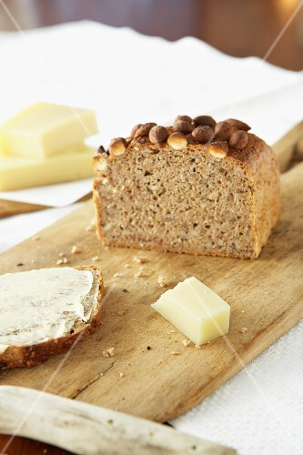 Sliced multigrain bread with almonds on a wooden board with a piece of cheese
