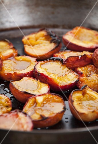 Fried nectarines halves in a pan (close-up)
