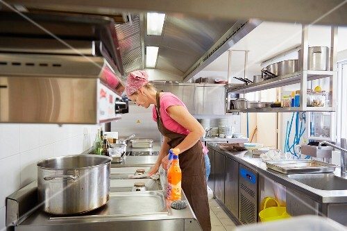 A woman wearing a headscarf cleaning in a restaurant kitchen