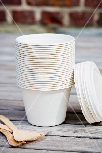 A stack of take-away cups and wooden forks on a table outside