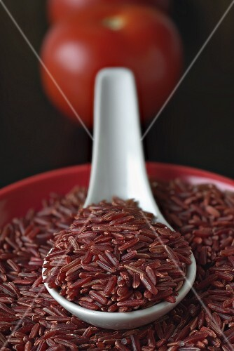 Red rice in a bowl and on a porcelain spoon (close-up)