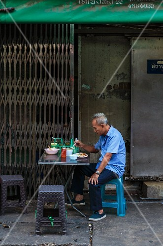 An oriental man having breakfast in the street (Thailand)