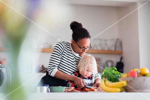 A mother and son cutting fruit together in the kitchen