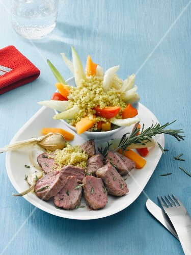 Lamb fillet with rosemary served with quinoa on a bed of vegetables