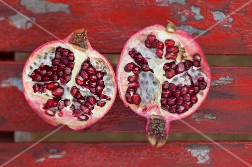 A halved pomegranate on a red wooden surface (seen from above)