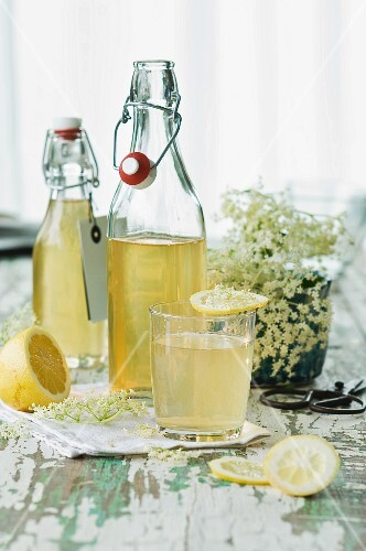 Bottles of elderflower syrup and a glass of elderflower cordial with a slice of lemon