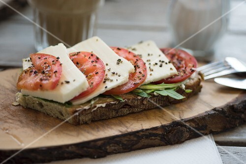 Olive bread topped with tomatoes, mozzarella, rocket and black pepper