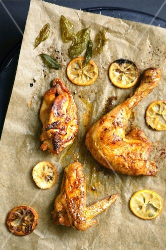 Chicken with lemon slices and sage on baking paper