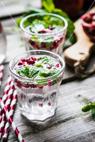 Detox drinks with lemon water, mint and pomegranate seeds