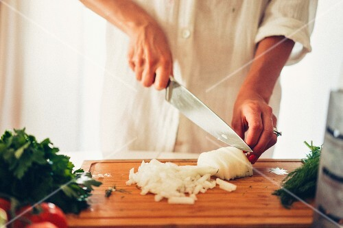 A woman chopping an onion in a kitchen