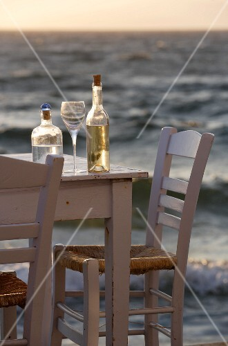 Table with wine bottle and glass on the waterfront at dusk, Little Venice, Mykonos Town, Greece