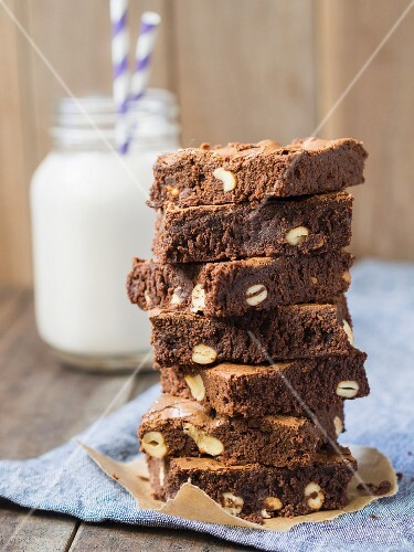 A stack of wholegrain organic brownies with cashew nuts and a glass of milk in the background