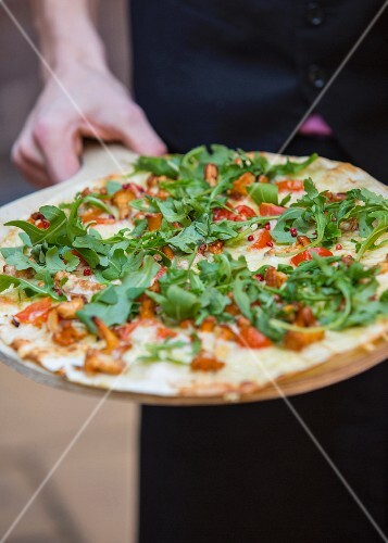 Tarte flambée with rocket, cherry tomatoes, chanterelle mushrooms and sour cream