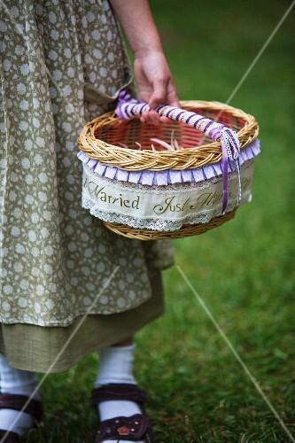 Girl in meadow holding basket of flowers