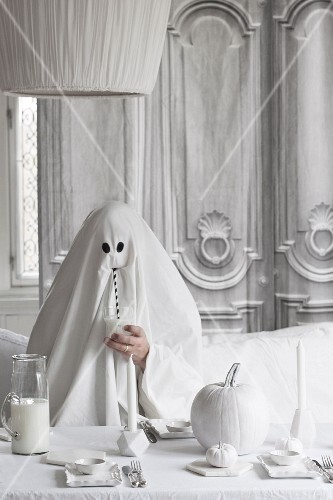 Person disguised as ghost drinking through a straw next to Halloween decorations on table