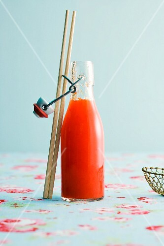 A bottle of chilli sauce with chopsticks