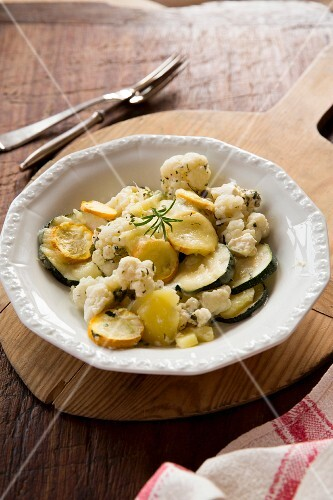 A portion of courgette and cauliflower bake with potatoes and rosemary