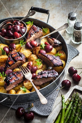Duck breast with five spice powder on potatoes and cherries