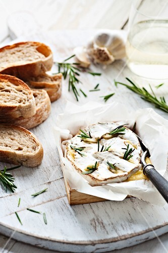 Baked cheese with rosemary and garlic served with baguette