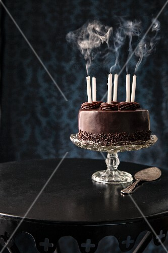 A chocolate cake with blown-out birthday candles on a cake stand