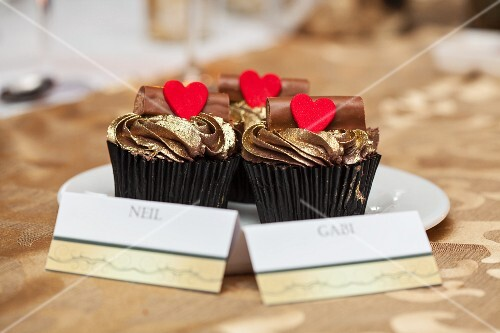 Cupcakes with golden frosting, chocolate logs and hearts at a wedding