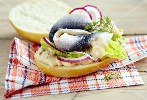 Herring on a burger bun with red onions