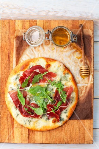 A pizza with gorgonzola, ham, rocket and honey