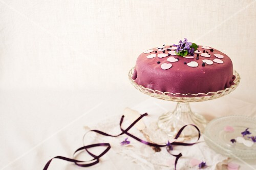 A cake with a violet marzipan coating
