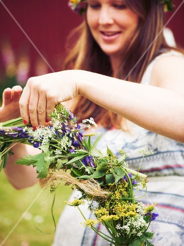 Woman tying wreath of flowers for midsummer festival
