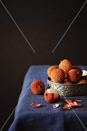 An arrangement of lychees in a metal bowl on a table