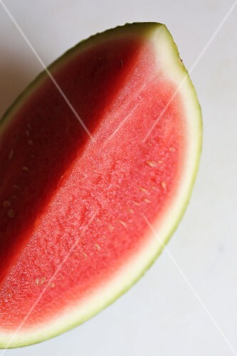 A wedge of watermelon on a marble surface