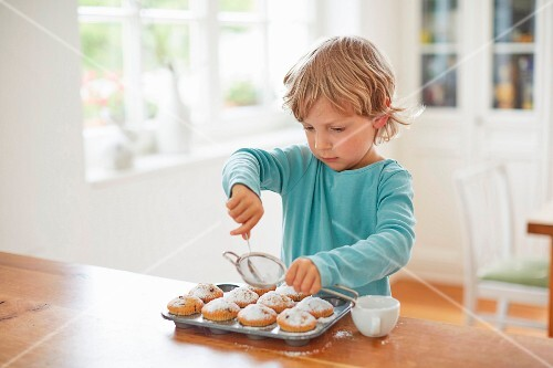 A young boy dusting muffins with icing sugar