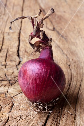 A red onion on a wooden surface