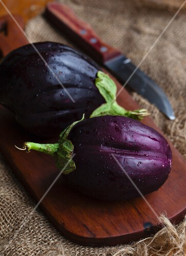 Two fresh aubergines on a wooden board