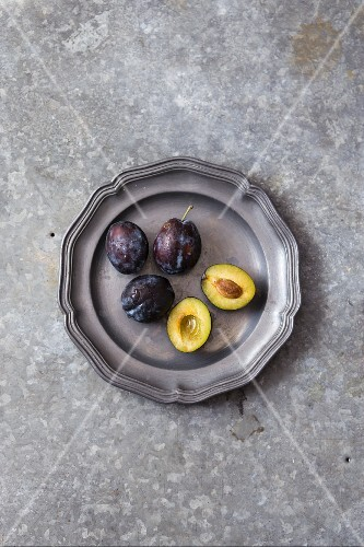Fresh plums on a metal plate