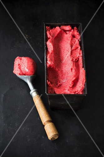 Berry sorbet in an container with an ice cream scoop