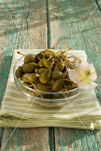 Caper fruits in a glass bowl on a wooden table