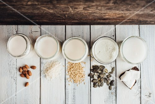 Various types of vegan milk in jars next to almonds, rice, oats, pumpkin seeds and coconut