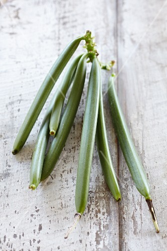 Green vanilla pods on a wooden surface