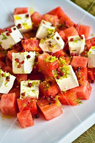 Feta and watermelon salad garnished with lime zest and pink peppercorns