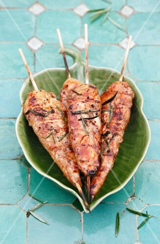 Grilled chicken skewers on a leaf-shaped plate