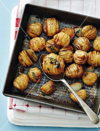 Hasselback potatoes with herbs on a baking tray (seen from above)