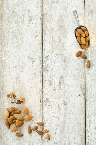 Almonds, shelled and unshelled, on a wooden surface and on a scoop