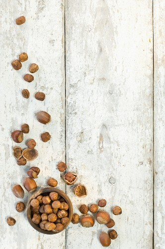 Hazelnuts in a wooden bowl and on a wooden surface