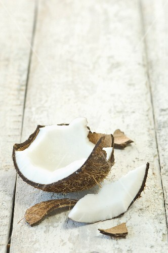 A broken coconut on a wooden surface